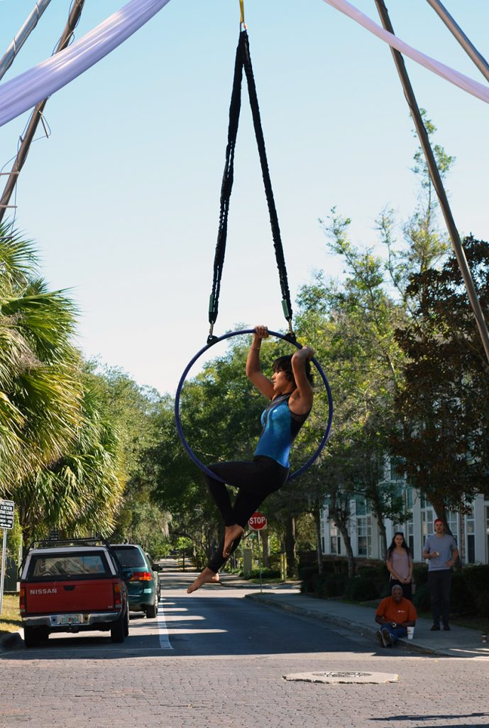 """An aerialist performs at the Gainesville Downtown Festival and Arts Show Saturday. The S-Connection Aerial Arts team performed regularly through the day as onlookers """"oh'd and ah'd."""" (Photo by Virginia Annable)"""