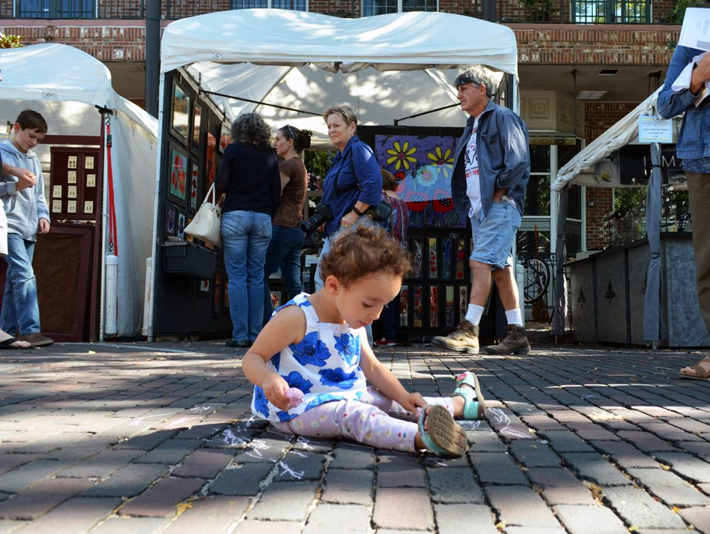 Lillian Van Hoosear draws with chalk at the Gainesville Downtown Festival and Arts Show Saturday. While other viewed the art, Lillian made her own children's area in the middle of the road. (Photo by Virginia Annable)