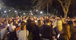 "Attendees of the memorial Monday that celebrated the life of University of Florida student Abby Dougherty reflect on her life outside the UF Food Pantry, where Dougherty volunteered. ""These candles remind us how bright Abby shined,"" Kira Ben-Hamo, a UF Rec Sports co-worker of Dougherty's, told those gathered. (Madison Belfour/WUFT News)"