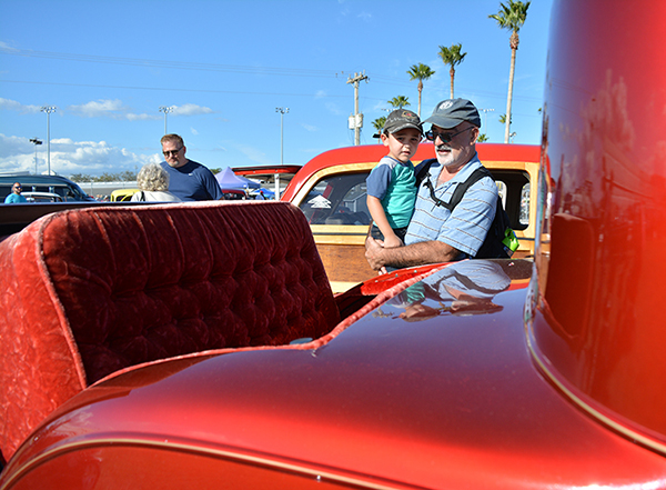"""Julian Cantillo holds his grandson, Alexander Isidro, to see inside the back trunk of """"Dot's Car."""" Cantillo said he's been to about eight shows and hopes to share the tradition with his grandson. (Elena Castello/WUFT News)"""