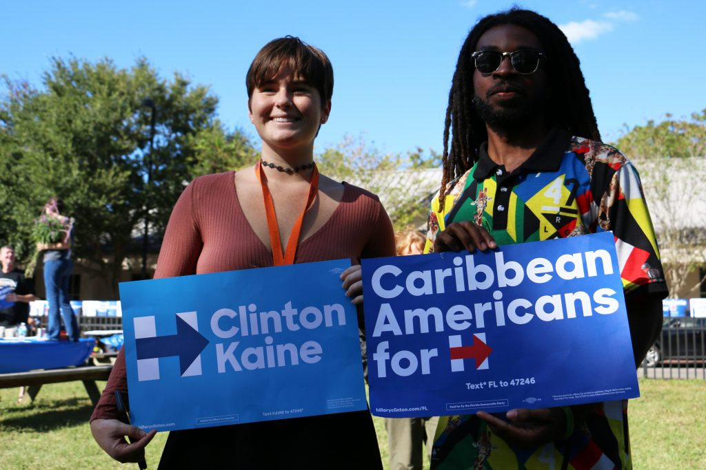 "University of Florida student Zoe Davis, left, and Daytona State College student Armoni Stefan hold signs supporting Hillary Clinton. After stopping by the early voting location, Bill Clinton briefly visited Carribean Queen restaurant in Gainesville. Lots of ""Carribean Americans for Hillary"" signs were handed out there. (Rachel Wang/WUFT News)"