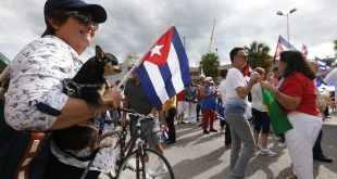 Anita Garcia (left) and her dog Louis look on as fellow members of the Cuban community react to the death of Fidel Castro Saturday in the Little Havana area in Miami. Just three days after Castro's death, the first Florida-Cuba flight took off. (AP Photo/Wilfredo Lee)