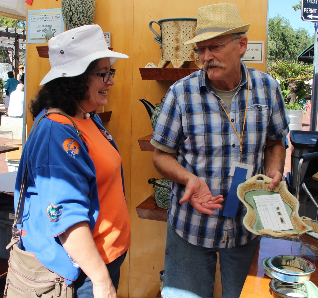 Ira Burhans talks to Betsy Summers about one of his handmade stoneware pottery pieces. He has been making pottery for 37 years. (Photo by Kayla Ziadie)