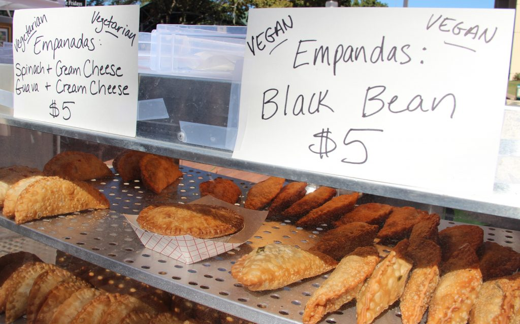 The smell of kettle corn, funnel cakes, homemadeempanadas andblooming onions wafted throughthe streets of downtown Gainesville duringthe35thannual Downtown Festival and Art Show this past weekend. High Springs Orchard and Bakery sellspastries such as spinach and cream cheese empanadas and vegan black bean empanadas.(Photo by Kayla Ziadie)