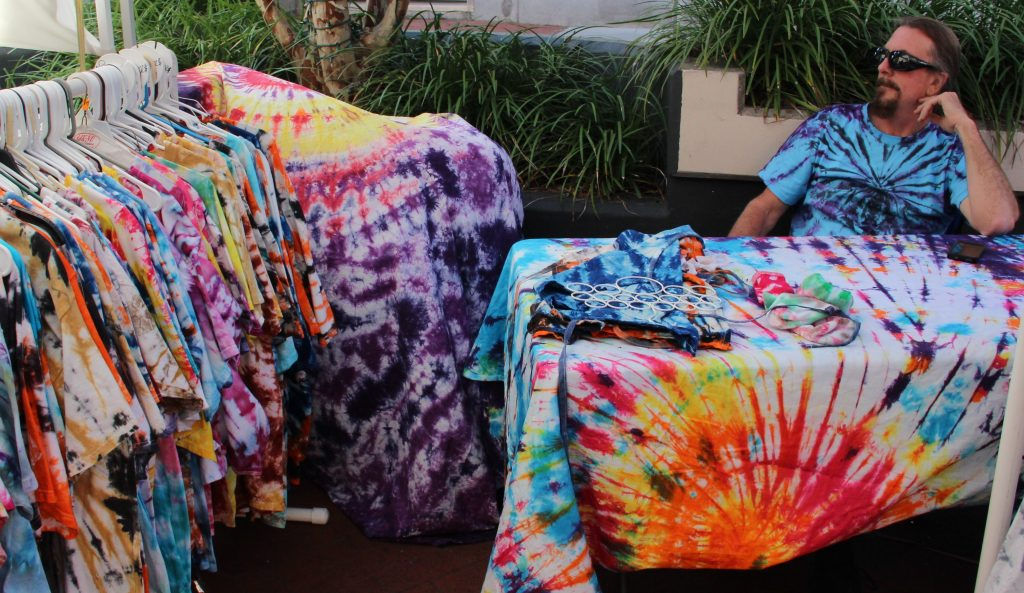 "Scott Allen sits among the tie dye shirts he has made at his Groovy Gator Tie Dye tent. Allen is the owner of Groovy Gator Tie Dye, a side job to being an 11th grade U.S. History teacher at Buchholz High School. He had hundreds of tie dye shirts he makes by hand on racks to be sold. ""This is my first time at the festival, but I've been making tie dye shirts for about three years,"" Allen said. ""It definitely takes practice, but I love what I do."" (Photo by Kayla Ziadie)"