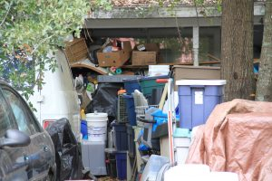 Boxes of items that Doug Englert has collected over the years are piled high in his front yard. (Mariana Riquezes/WUFT News)