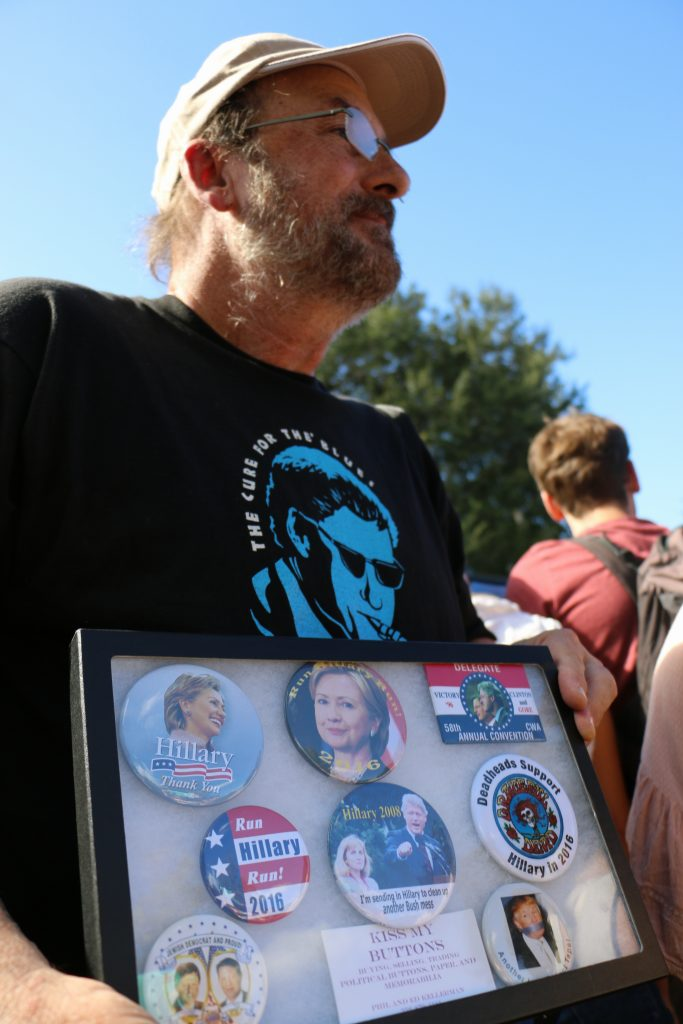"Ed Kellerman holds a framed collection of campaign buttons as he waits for Clinton. He later handed the collection to Clinton. ""I want you to have it,"" he said to Clinton. (Rachel Wang/WUFT News)"