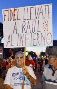 "Nestor Ramos holds up a sign reading ""FIDÉL LLEVATE RAÚL AL INFIERNO"" or ""FIDEL TAKE YOUR BROTHER TO HELL"" on Calle Ocho. Ramos came to the United States from Cuba in 1958. (Grace King/ WUFT News)"