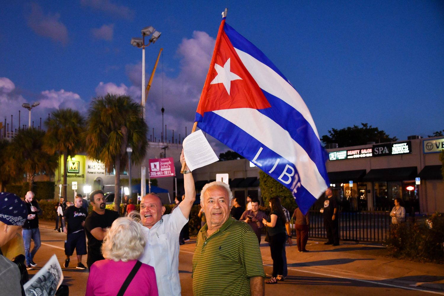 "A man waves a Cuban flag with the word ""LIBRE,"" or ""FREE"" in English, on it. He was one of about 200 people who gathered on Calle Ocho Sunday night. (Grace King/ WUFT News)"