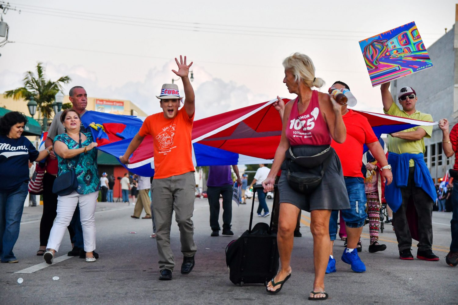 A guy throws up his hand as he marches down Calle Ocho with the giant Cuban Flag. (Grace King/ WUFT News)