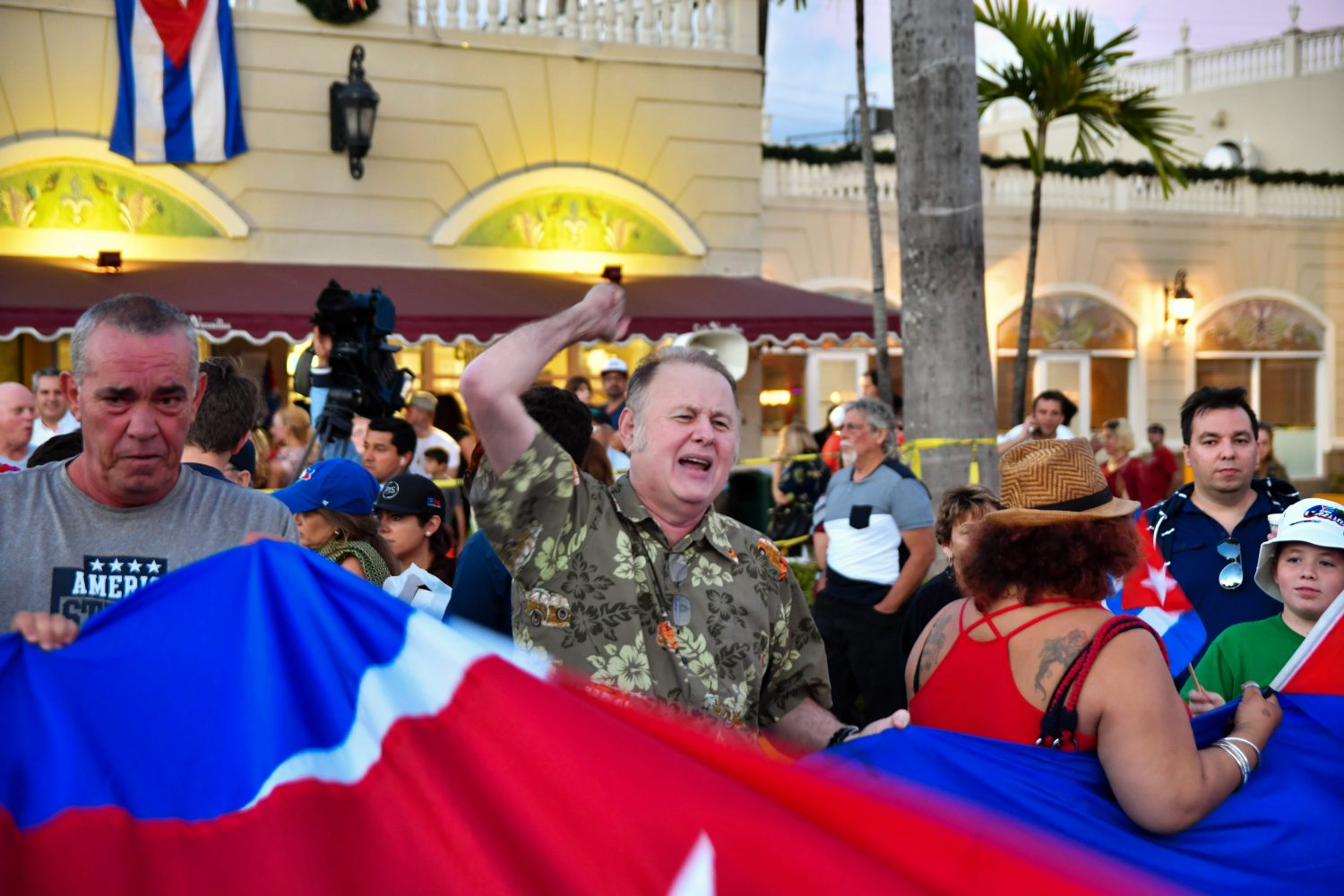 Miguel Inclan throws up his fist while holding onto the Cuban Flag with his other hand. He left Cuba in 1980. (Grace King/ WUFT News)