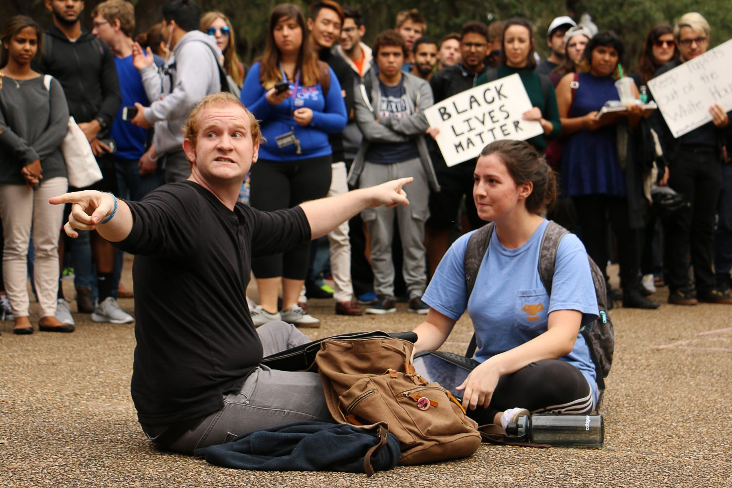 "Nick Simmons (left) and Alison Wilfong, who don't know one another, sit together in the middle of the crowd. Though they discovered they disagree politically Simmons they agreed that yelling doesn't solve anything. ""It went from a protest to a circus and kind of lost its meaning,"" he said. ""So we decided to sit in the middle and indulge in the universal love of memes."" (Rachel Wang/WUFT News)"