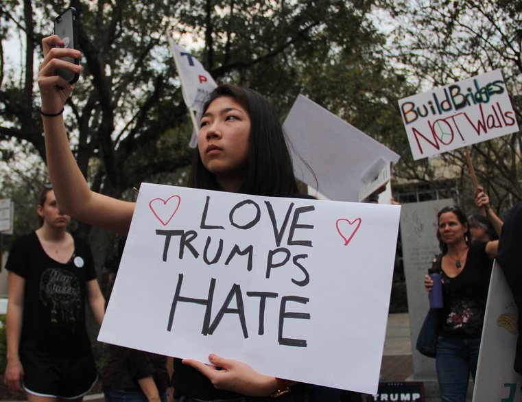 """Rebecca Ragan, an 18-year-old freshman student at the University of Florida,records the Freedom from Fear marchcrowd in Bo Diddley Plazawhile holding an anti-Trump sign. """"This was a really disappointing election, and it's disappointing how Trump won with all his hate and bigotry,"""" she said. (Kayla Ziadie/WUFT News)"""
