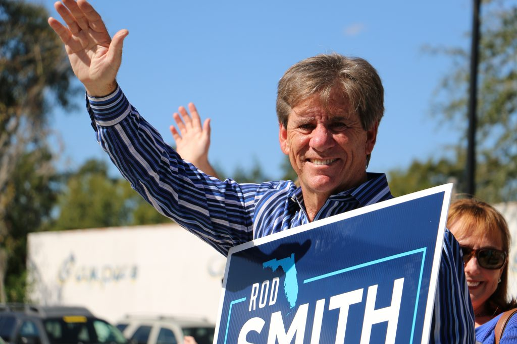 Rod Smith, the District 8 Democratic candidate for the Florida State Senate, greets voters in front of an early voting place in Gainesville, where Clinton made a stop Saturday. (Rachel Wang/WUFT News)