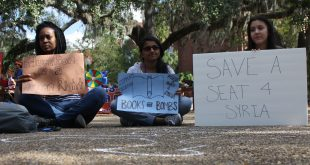(From left) Mashli Fleurestil, 22, Rebecca Prince, 18, and Mariana Suguieda, 19, participate in a silent demonstration Tuesday at the University of Florida that campaigned for the university to offer five scholarships to Syrian refugees. (Michaela Steakley/WUFT News)