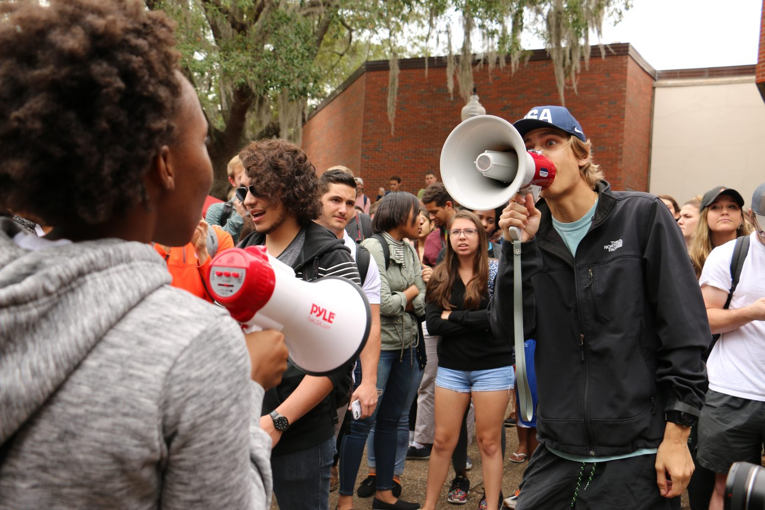 Cullen Powers (right) yells through a bullhorn at an anti-Trump protestor.