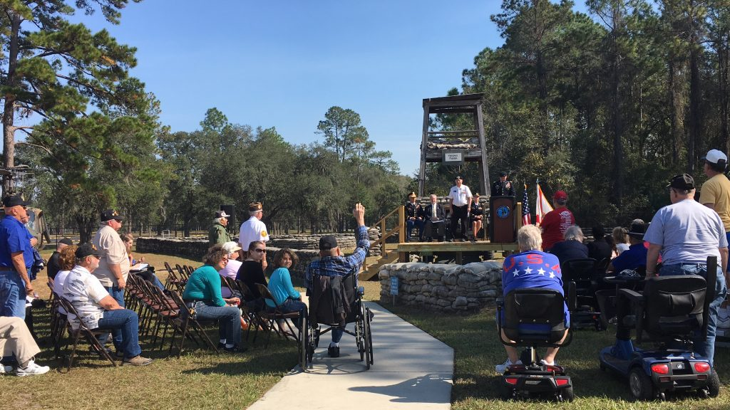"""Veterans stand or raise their hand as the crowd applauds at Camp Blanding's Annual Veteran's Day ceremonies Nov. 11. This year's event had a focus on """"welcoming home"""" all Vietnam veterans in attendance. (Gabriela DeAlmeida/WUFT News)"""