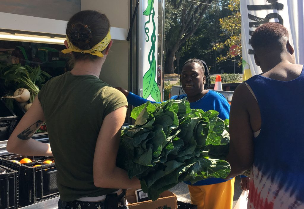 Oak Park residents pick collared greens from the Fresh Wagon's shelves; they sold out in the first ten minutes of the mobile market's opening. (Victoria Todd/WUFT News)