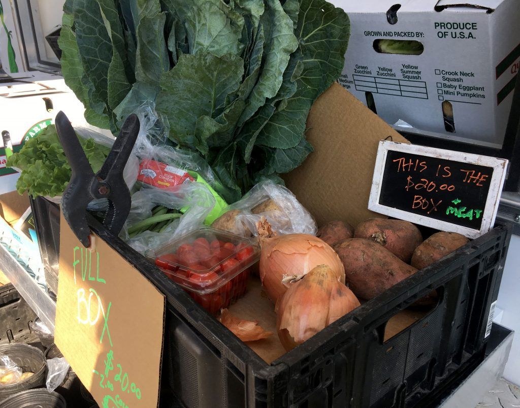 Food boxes sat at the end of the line filled with a large bunch of collards, lettuce, onions, tomatoes, beans, potatoes, corn bread mix and a cornbread recipe. Priced at $18 with a coupon, Waite said retail markets would price the bundle at $27. (Victoria Todd/WUFT News)