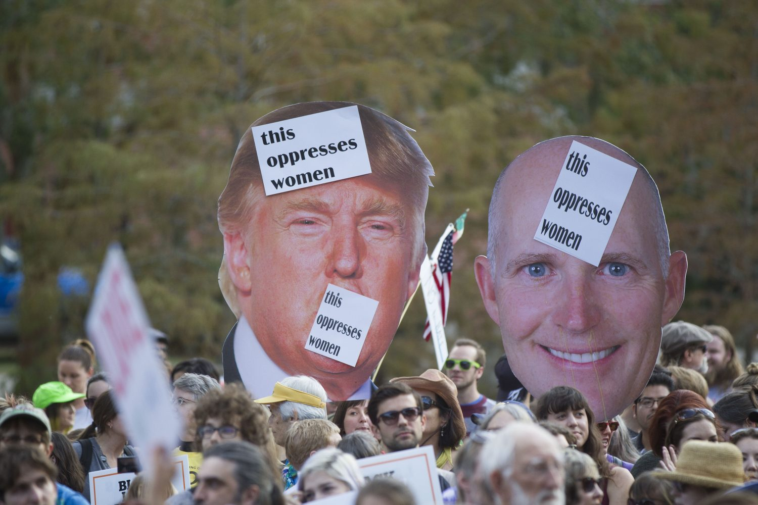 Protestors hold cutouts of Donald Trump and Florida Gov. Rick Scott as they gather outside the University of Florida's football stadium. (Michael Stone/WUFT News)
