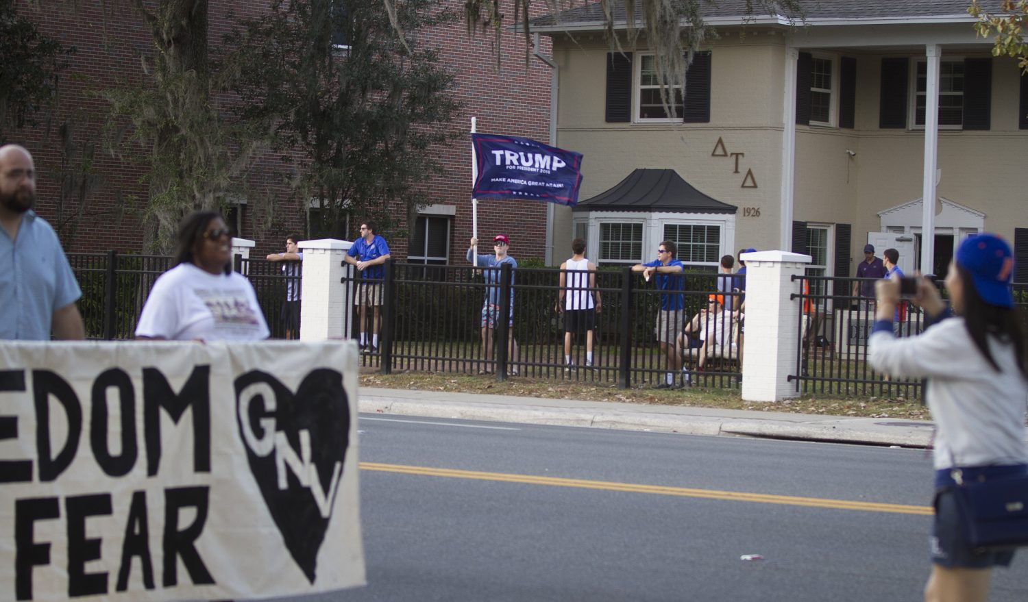 A man at the Delta Tau Delta house across from the University of Florida waves a Donald Trump flag as the protestors walk by. (Michael Stone/WUFT News)