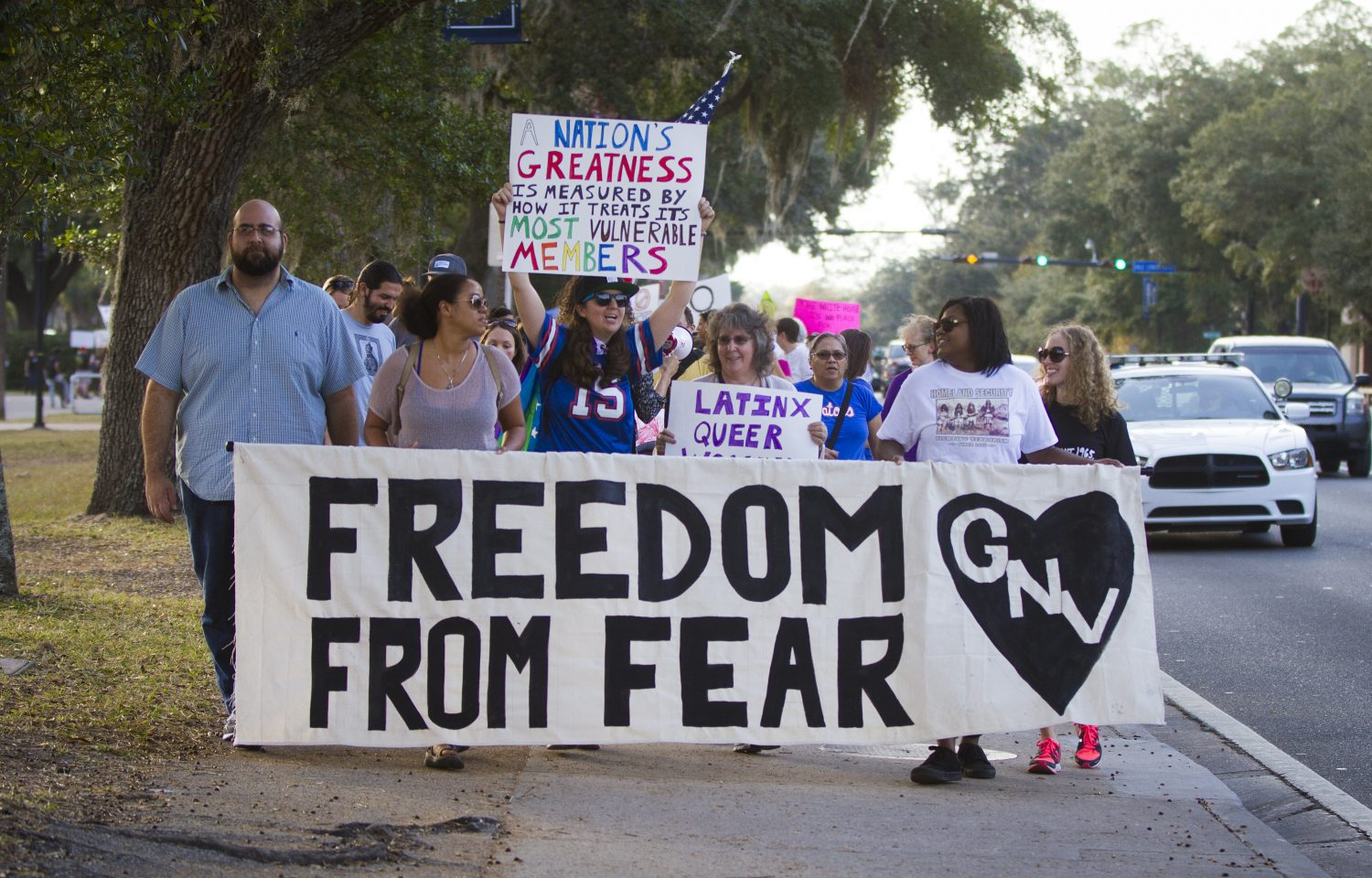 """The protestors at the head of the line hold a sign that says """"Freedom from fear."""" (Michael Stone/WUFT News)"""