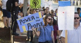 "A woman holds a sign reading ""Power to the people"" as anti-Donald Trump protestors march along University Avenue in November 2016. The same group that organized that protest has put together another to coincide with Trump's inauguration Friday. (File/WUFT News)"