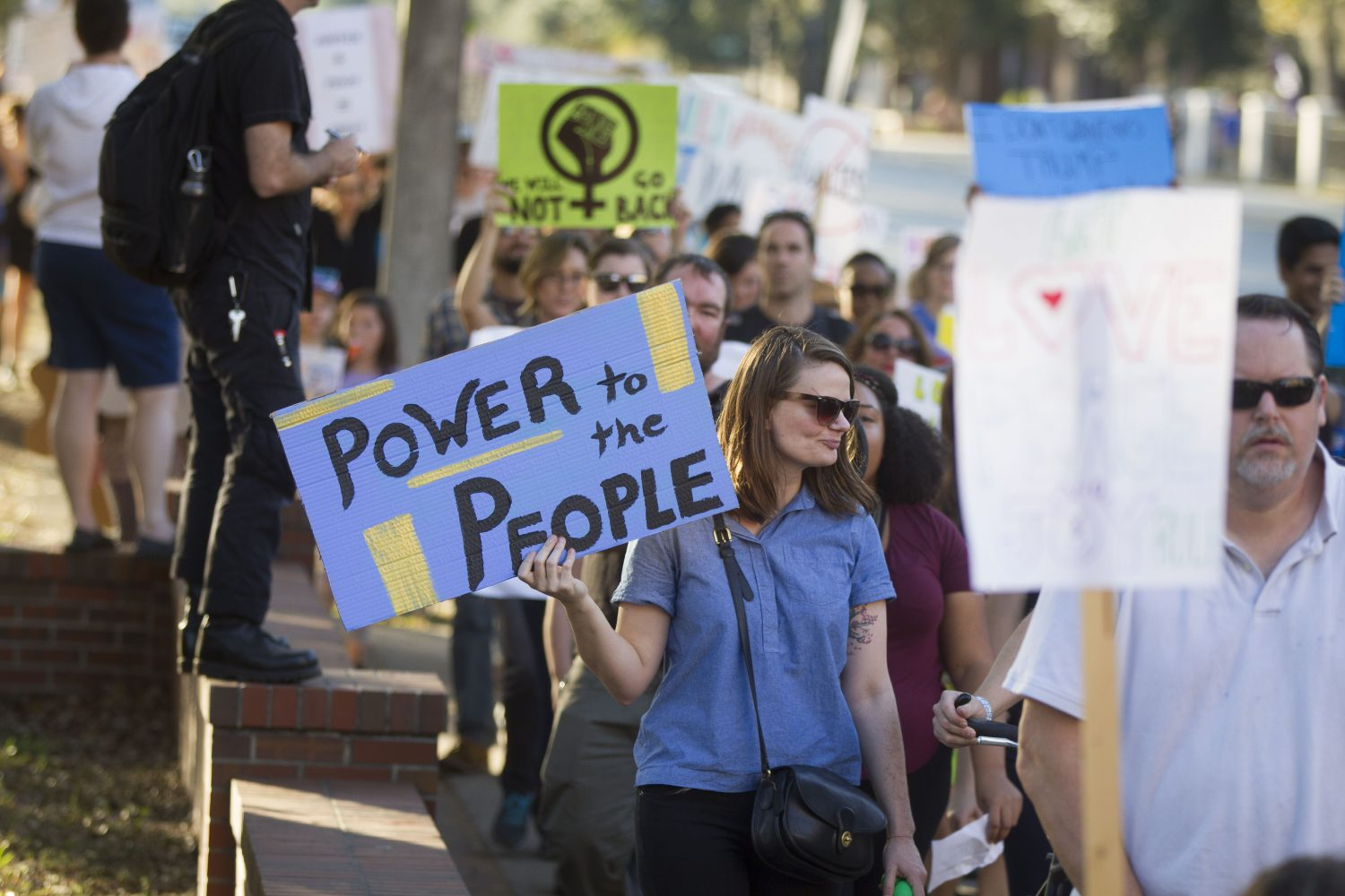 "A woman holds a sign reading ""Power to the people"" as protestors march along University Avenue. (Michael Stone/WUFT News)"