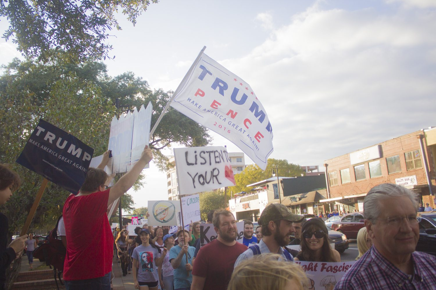 Trump supporters wave a flag and signs as the protestors pass Gainesville's Midtown area. (Michael Stone/WUFT News)