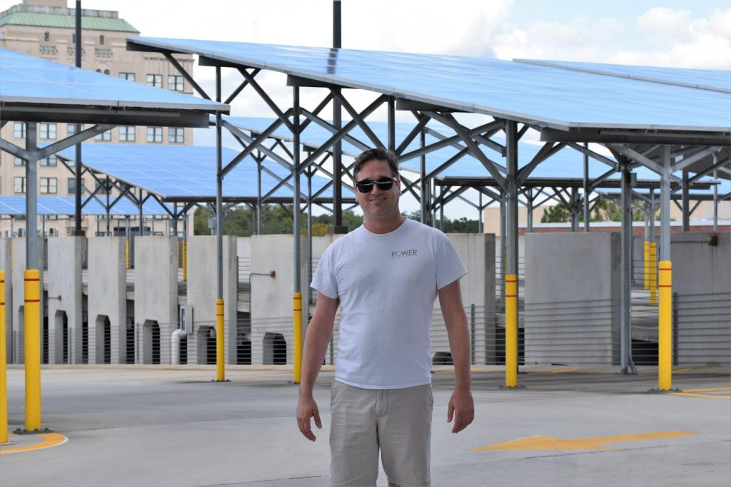 Michael Collins, the director of sales at Power Production Management stands proudly among solar panels his company installed. These solar panels are located on the roof of a parking garage for The Continuum in Gainesville. (Isabella Sorresso/WUFT News)
