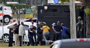 Hostages released from inside the Community First Credit Union run to police officers behind a SWAT van outside the bank in Jacksonville, Fla., on Thursday Dec. 1, 2016. (Bob Mack  /The Florida Times-Union via AP)