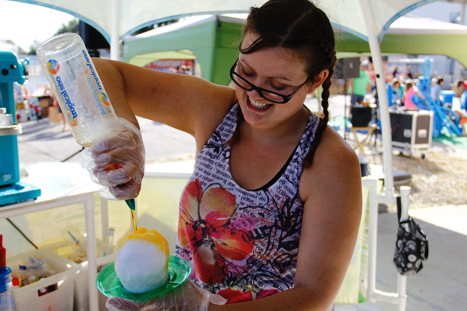 Leanne Ward, 29, pours mango-flavored syrup on a snow cone on this hot December day. (Photo by Lauren Gandy/WUFT News)