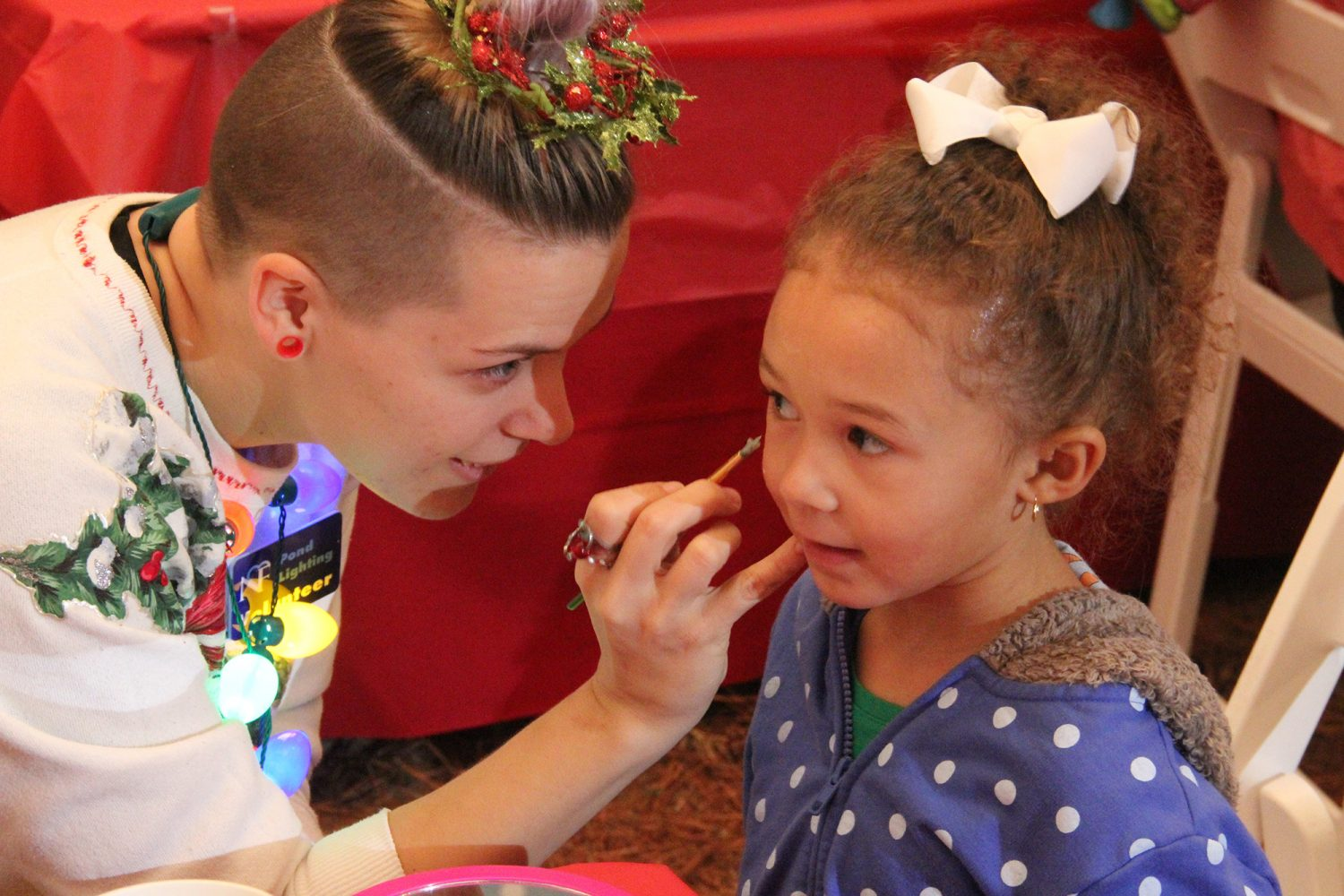 Within the face painting tent, a North Florida Regional Medical Center volunteer paints a snowman on a young girl's cheek at the Pond Lighting Festival Friday night. (photo by Visshaael Patel)