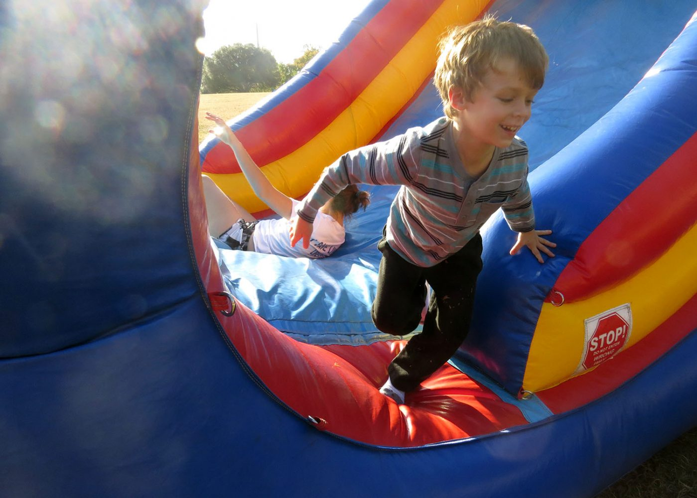 SLIDING FOR JOY- Jameson Worthington, 5, climbs out of an inflatable after sliding down it with his mom, Jessica Worthington, at Keyes Governing Body's Bounce Your Stress Away event on Flavet Field on Sunday, December 4, 2016. (photo by Katelyn Newberg)
