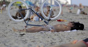 Chris Borchetta, of Miami Beach, Fla., takes advantage of a sunny day as he lies on the beach, Wednesday, Dec. 14, 2016, in Miami Beach, Fla. Temperatures are above average and in the mid-80's in South Florida as an arctic cold front moves from the Plains to the Ohio and Tennessee Valleys, and towards the mid-Atlantic and Northeast by Thursday. (AP Photo/Lynne Sladky)