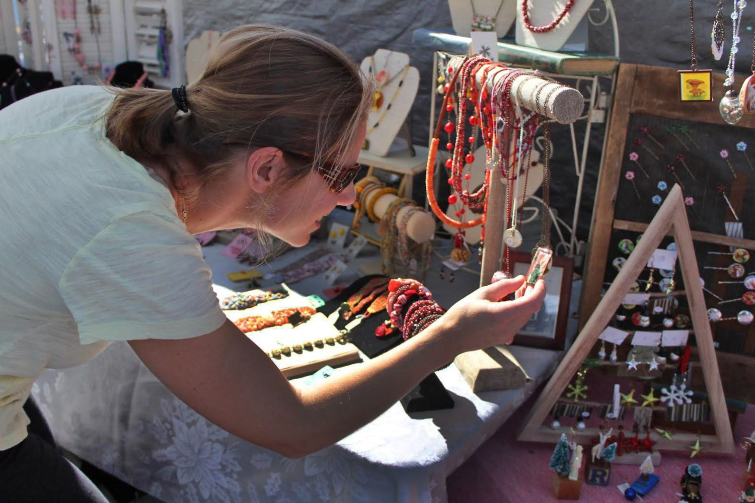 Megan Saillant, an attendee of the GLAM Craft Show, browses for jewelry at one of the booths. Saillant purchased a wooden animal for her daughter. (Photo by Sophie Smadbeck/WUFT News)