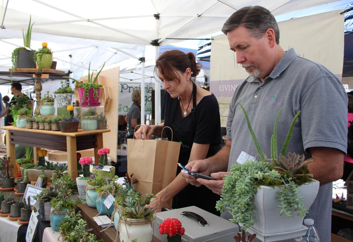 Dee and Phil Mullen, owners of the floral design company Willow Gardens, prepare to check out customers. This was the Mullens' first year at the GLAM Craft Show. (Photo by Sophie Smadbeck/WUFT News)
