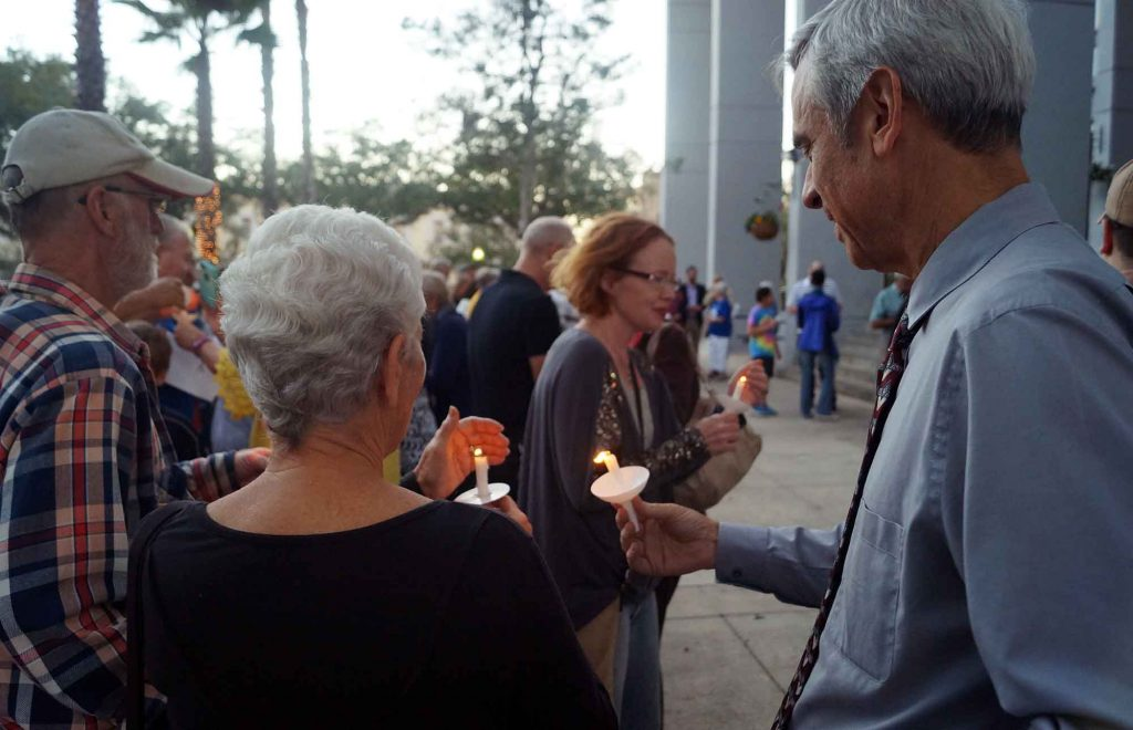 Two attendees protect their candles from the breeze. (Jack DaSilva/WUFTNews)