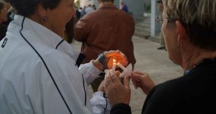 Former University of Florida faculty, Sally Chesrown lights Jane Day's candle with hers on the steps of City Hall at the Light In The Darkness gathering on Tuesday evening (Jack DaSilva/WUFT News).