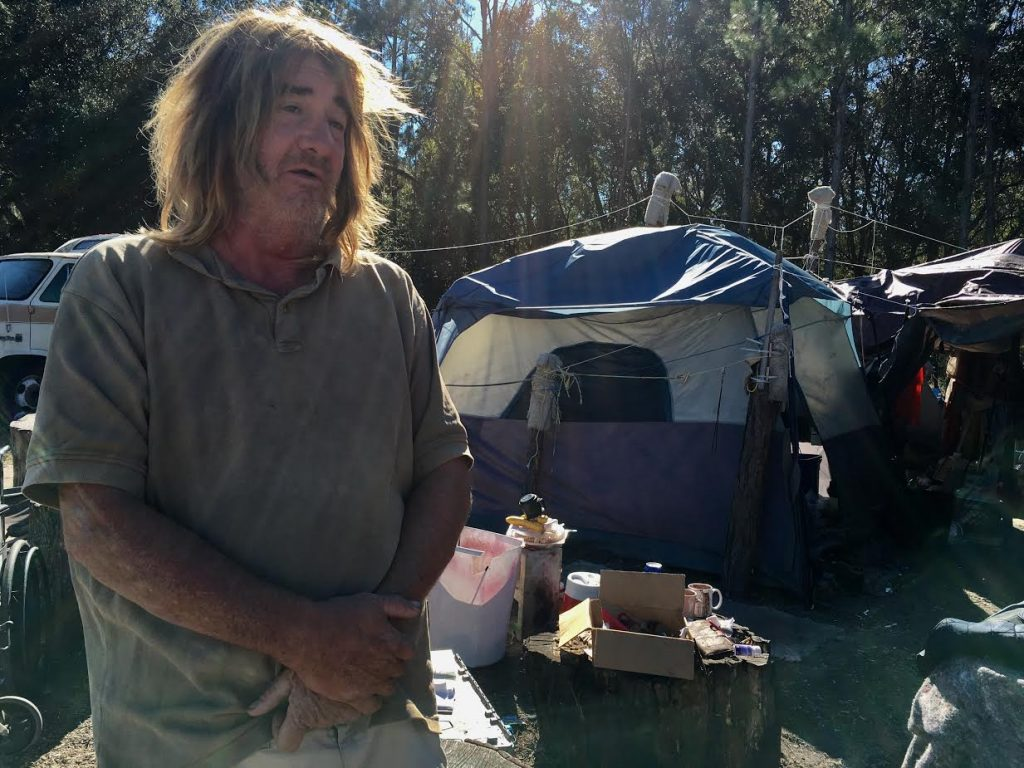Peter Dannenhoffer, 54, lives in a tent in Dignity Village with three other people. He put up the tarp to not only keep out rain, but to prevent the wind from blowing through the tent. (Antara Sinha/WUFT News)
