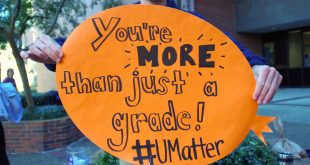"""Lawson Jaffe, 22, a fourth-year biology and economics student at UF, holds up an orange sign reading """"You're more than just a grade"""" while tabling outside of Marston Library on Friday, Dec. 9. Jaffe, a Campus Diplomat, was tabling alongside U Matter, We Care ambassadors to encourage students before final exams."""