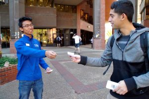 "Raymund Gaviola, a U Matter student ambassador, hands out fliers on Dec. 9 to students walking past Marston Library. The fliers had words of encouragement on them, such as ""Never stop believing in yourself, because the Gator Nation believes in you."""