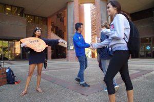 Shahreen Zaman, 21, a fourth-year anthropology major, hands out fliers and candy alongside Raymund Gaviola, a U Matter student ambassador.