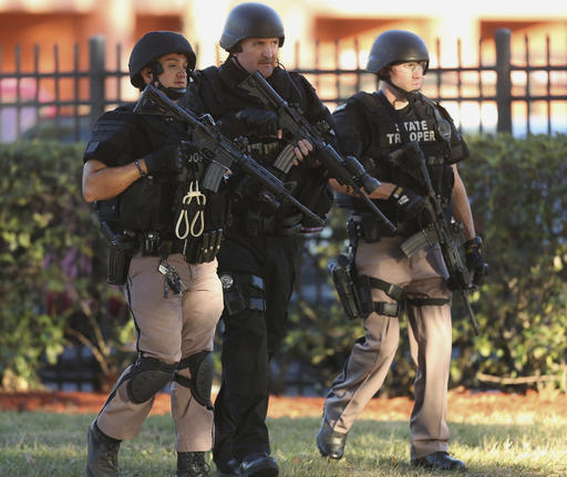 Law enforcement officers conduct a door-to-door search at an Orlando apartment complex Monday. (Stephen M. Dowell/Orlando Sentinel via AP)