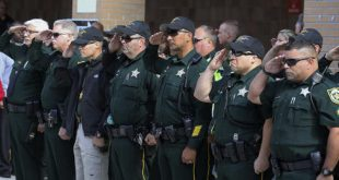 Orange County sheriff deputies salute as the body of Orange County Sheriff's Office Deputy First Class Norman Lewis was transported from Orlando Regional Medical Center after the deputy was killed in the line of duty Monday (Joe Burbank/Orlando Sentinel via AP)