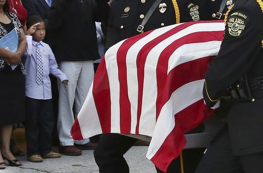 A young boy, left, salutes as the flag-draped casket is carried during funeral services for Orlando Police Master Sgt. Debra Clayton at the First Baptist Church in Orlando, Fla., Saturday. Authorities say Clayton was gunned down outside a Wal-Mart store in Orlando last Monday after she approached 41-year-old Markeith Loyd, who was wanted for the murder of his pregnant girlfriend at the time.  (Stephen M. Dowell/Orlando Sentinel via AP)