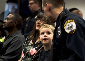 "Patrick Hopkins, 5, looks up at his dad during the Gainesville Police Department awards ceremony at the GPD headquarters on January 25, 2017. Officer Hopkins is among 93 people in the United States and Canada who received the Carnegie Medal in 2016. ""It was something I did on the job,"" Hopkins said, ""and they were nice enough to give it to me."" (Elle Beecher/WUFT News)"