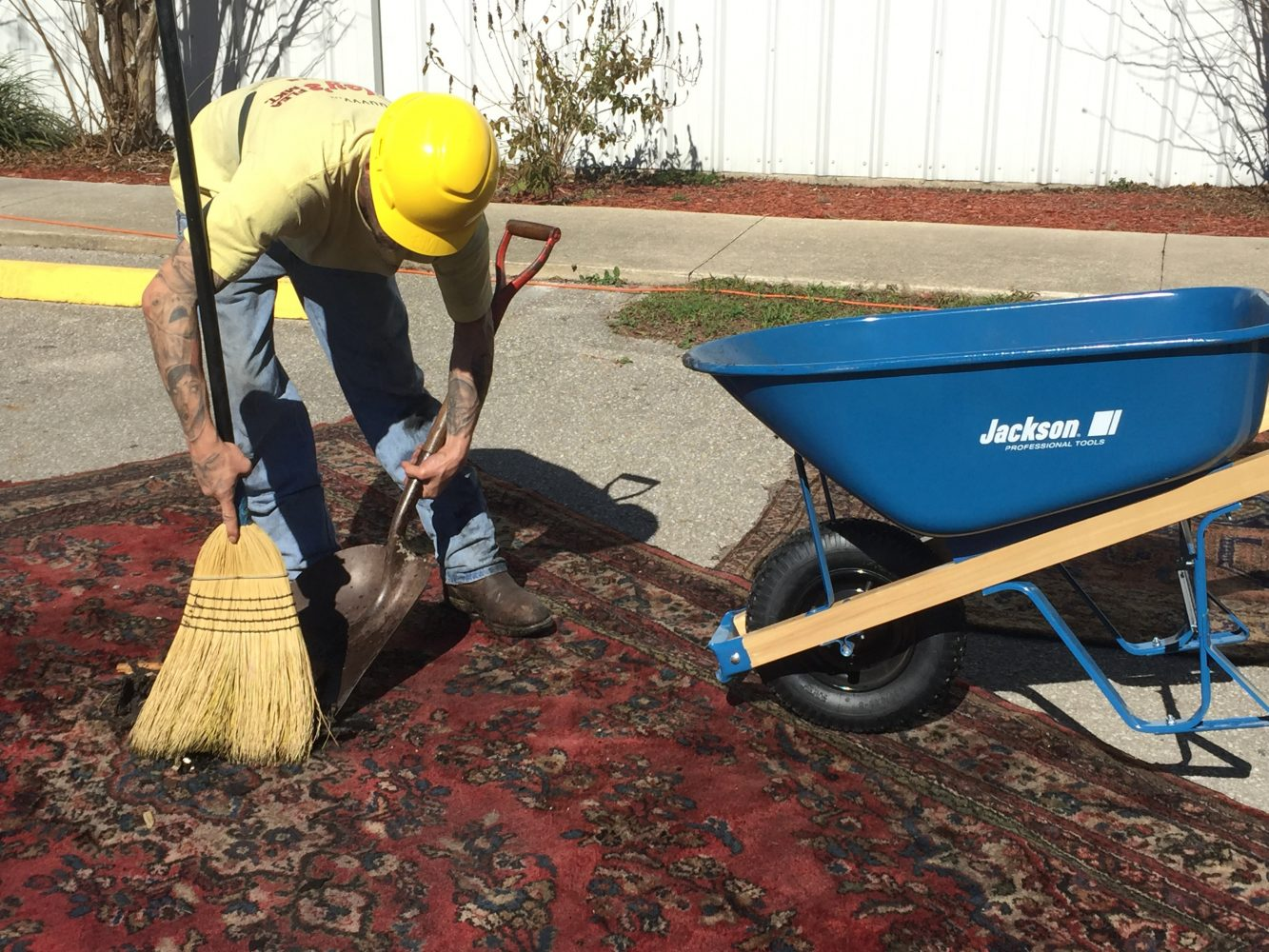 A worker sweeps us ashes off an antique rug. Workers attempted to clear the west side of the building to save some merchandise. (Gabriella Nuñez/WUFT News)