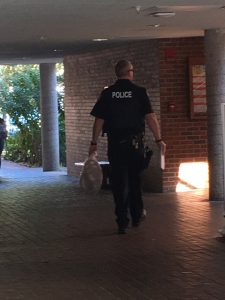 A police officer carries a noose in Weimer Hall today. (Lena Schwallenberg/WUFT News)