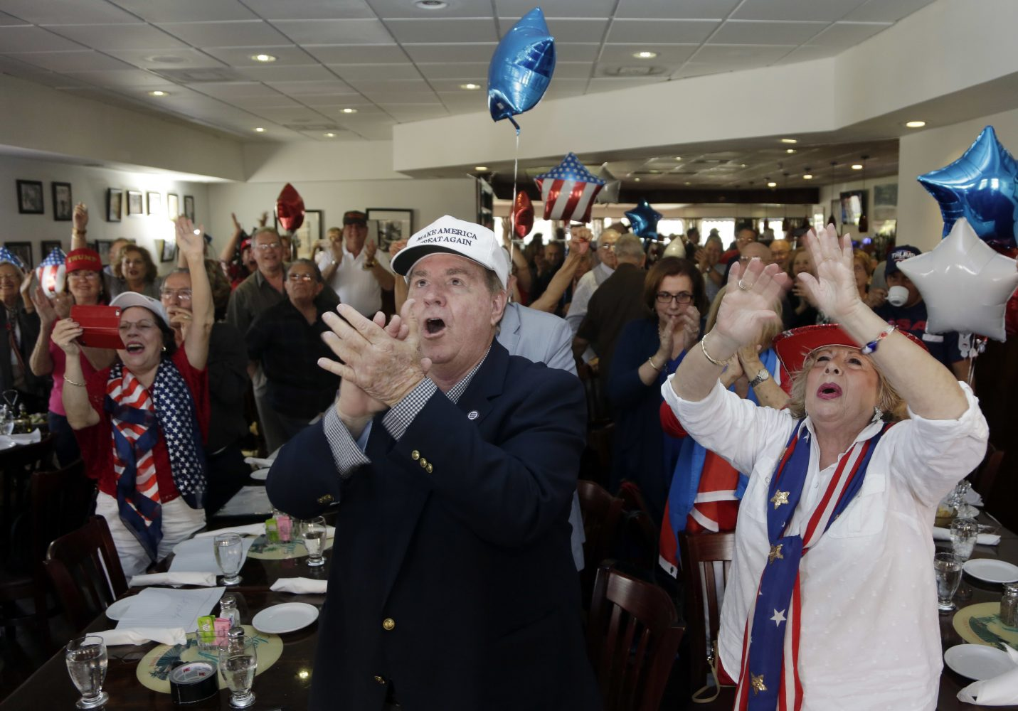 Frank de Varona, left, and Martie Mees, right, applaude as they watch a televised broadcast of the presidential inauguration of Donald Trump, Friday, Jan. 20, 2017, during a watch party organized by Hispanas for Trump in Miami. (AP Photo/Lynne Sladky)